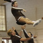 hlo in the air above Isaiah Gonzalez, left, and Hayley Honda during the squad's performance.
