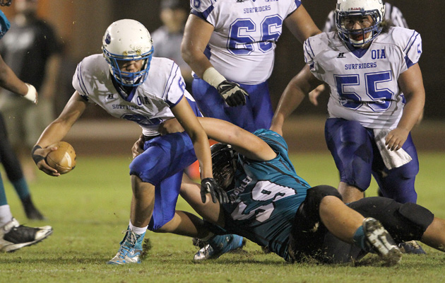 Kapolei's Masi Tunoa brought down Kailua QB Noah Auld in the second quarter on Friday. Auld and the Surfriders came back and finished strong. (Jay Metzger / Special to the Star-Advertiser)