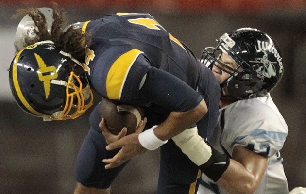 Kamehameha's Mika Tafua wrapped up Punahou quarterback Larry Tuileta last week. (Jamm Aquino/The Honolulu Star-Advertiser)