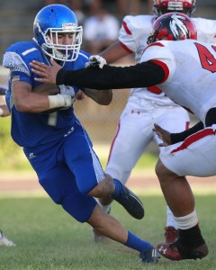 Moanalua running back Michael Feliciano tried to avoid Kahuku defensive lineman Salanoa-Alo Wily during Thursday's scrimmage. Honolulu Star-Advertiser photo by Cindy Ellen Russell