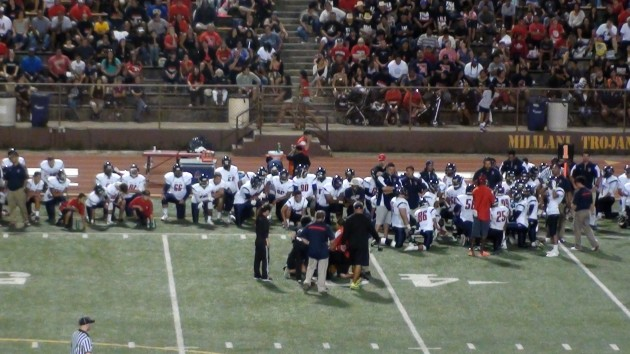 Saint Louis takes a knee during an injury timeout at Mililani.