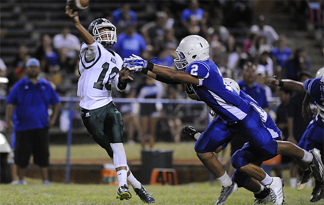 Aiea's Kobe Kato gets rid of the football under pressure by Kailua's Peter Albinio on Saturday. HSA photo by Bruce Asato
